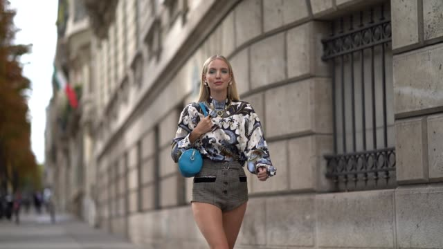 vídeos y material grabado en eventos de stock de leonie hanne wears earrings, a necklace, a white long sleeves hi-neck blouse with grey swan and mermaids print, brown prince of wales shorts, a blue... - cisne