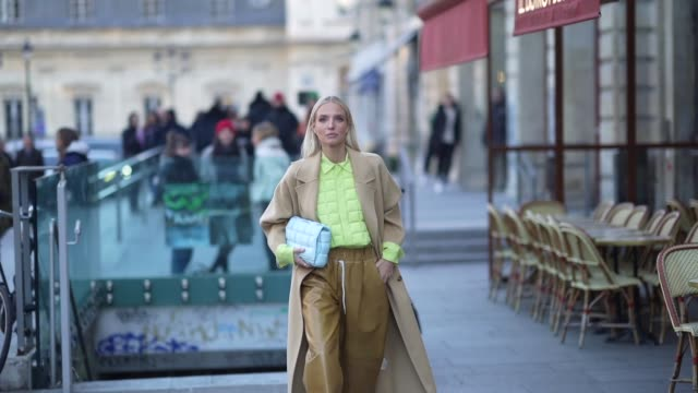 leonie hanne wears earrings, a pistachio-green quilted shirt, a beige coat, a bottega veneta light blue quilted clutch, light brown leather wide-legs... - paris fashion week - haute couture spring/summer 2020点の映像素材/bロール