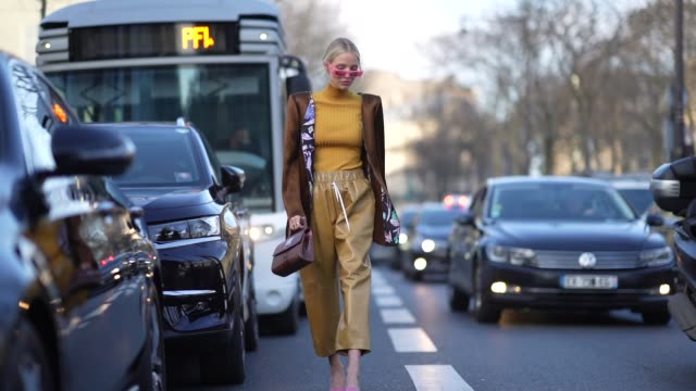 leonie hanne wears sunglasses a brown jacket with shoulder pads a yellow turtleneck pullover cropped pants a bag during paris fashion week haute... - turtleneck stock videos & royalty-free footage