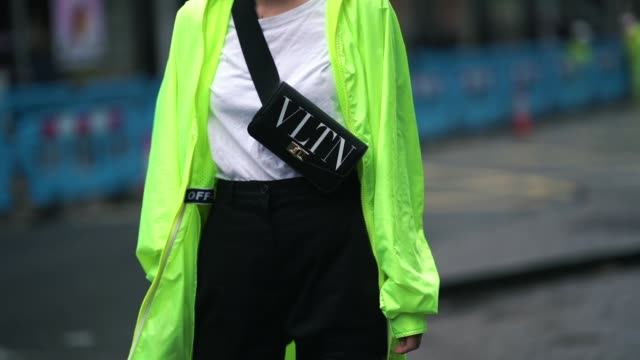 leonie hanne wears sunglasses, a valentino vltn shoulder strapped bag, a white t-shirt, a neon yellow green long jacket, black pants, balenciaga... - fashion week stock videos & royalty-free footage