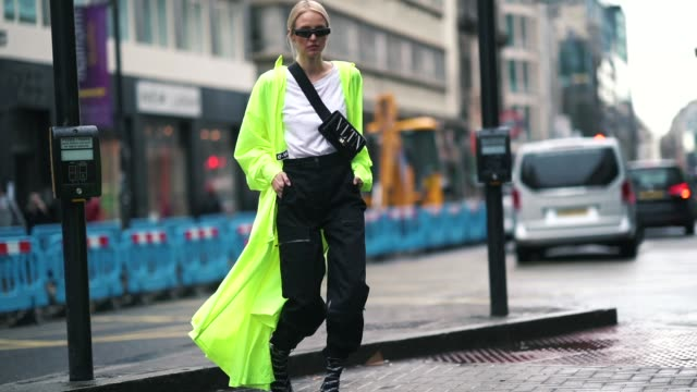 leonie hanne wears sunglasses, a valentino vltn shoulder strapped bag, a white t-shirt, a neon yellow green long jacket, black pants, balenciaga... - ストリートスナップ点の映像素材/bロール
