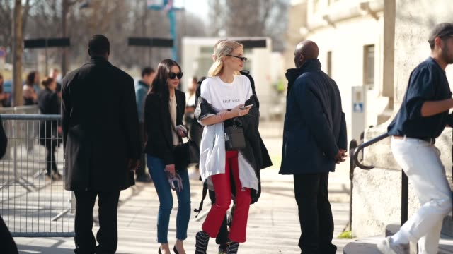 Leonie Hanne wears sunglasses a white tshirt 'Not Nice' red flare pants Balenciaga shoes a corset a small bag outside Unravel Project during Paris...