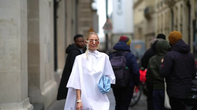 leonie hanne wears white sunglasses with chains, a white long dress, a pale blue puff bottega veneta bag, blue suede thigh high pointy boots, outside... - thigh human leg stock videos & royalty-free footage
