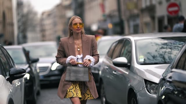 vídeos de stock, filmes e b-roll de leonie hanne wears yellow sunglasses a blazer jacket a golden necklace a white top a yellow pvc snake print skirt a gray bag black boots outside elie... - colar
