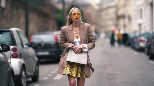 leonie hanne wears yellow sunglasses, a blazer jacket, a golden necklace, a white top, a yellow pvc snake print skirt, a gray bag, black boots,... - gray jacket stock videos & royalty-free footage