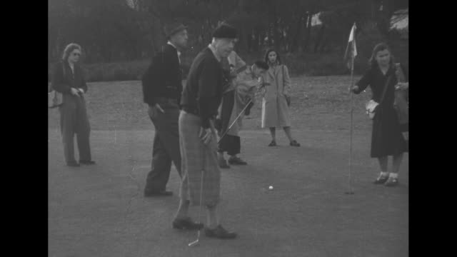leopold iii in fedora, left profile / he measures for putt / his right profile / all watch as the duke, wearing knickers and beret, attempts a putt,... - エドワード8世点の映像素材/bロール