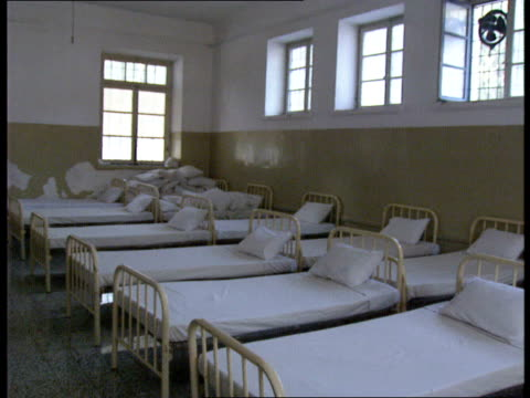 leros psychiatric unit scandal rows of beds very close together in hospital ward / female patient helping nurse make beds / water on floor of ward - psychiatric hospital stock videos and b-roll footage