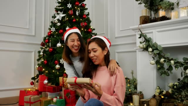 lesbian asian couple giving christmas gifts to each other happy sweet moment in living room at home in christmas festival. lifestyle lgbt women celebrate christmas concept. - unwrapped present stock videos and b-roll footage