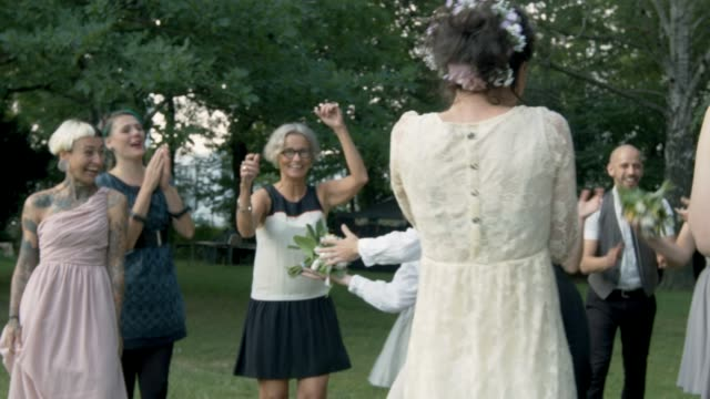 lesbian couple celebrating their wedding with their freinds - bouquet video stock e b–roll