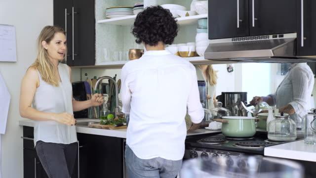 vidéos et rushes de lesbian couple cooking in kitchen - être debout