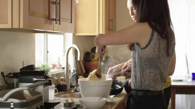 vidéos et rushes de a lesbian couple cooking pasta in their kitchen - droit