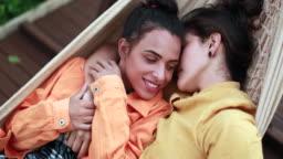 Lesbian couple cuddling lying on hammock