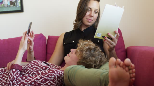 Lesbian couple cuddling on their couch while reading and looking at phone.