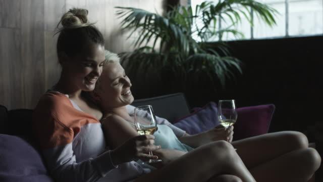 vídeos y material grabado en eventos de stock de lesbian couple drink white wine, medium - camisola