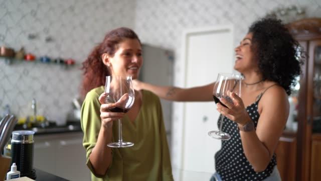 lesbian couple drinking wine portrait at kitchen - kitchen stock videos & royalty-free footage