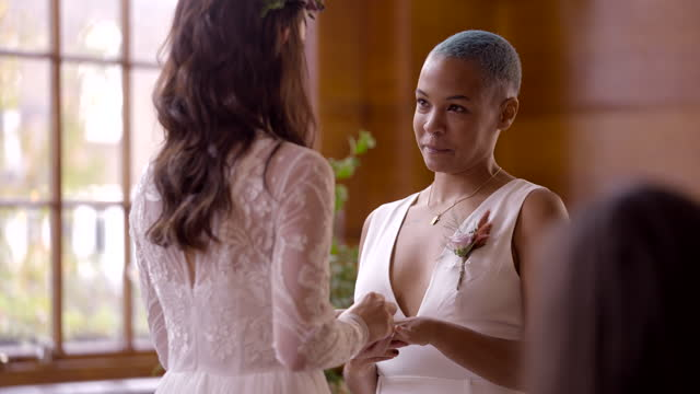 lesbian couple exchange rings and vows at wedding ceremony - waist up stock videos & royalty-free footage