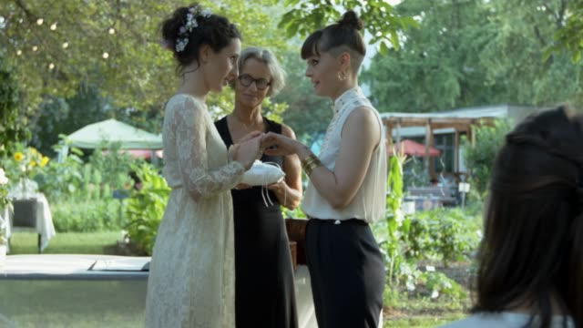 lesbian couple exchanging rings on their wedding - lesbe lesben stock-videos und b-roll-filmmaterial