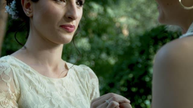 vídeos de stock e filmes b-roll de lesbian couple exchanging rings on their wedding - votos matrimoniais