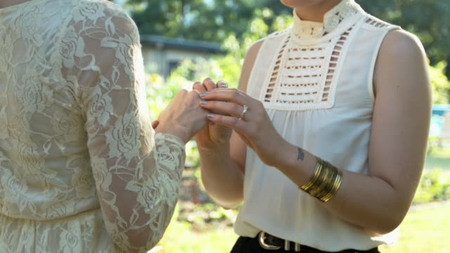 lesbian couple exchanging rings on their wedding - ehefrau stock-videos und b-roll-filmmaterial