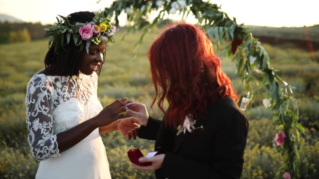 lesbian couple exchanging rings on wedding ceremony - wedding ring stock videos & royalty-free footage