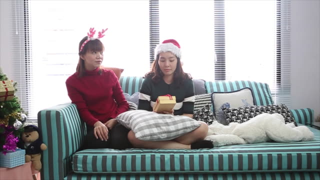 lesbian couple give gift in christmas event - 25 29 years stock videos and b-roll footage