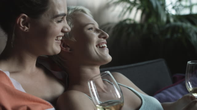 vídeos y material grabado en eventos de stock de lesbian couple hold white wine on couch, close up - camisola