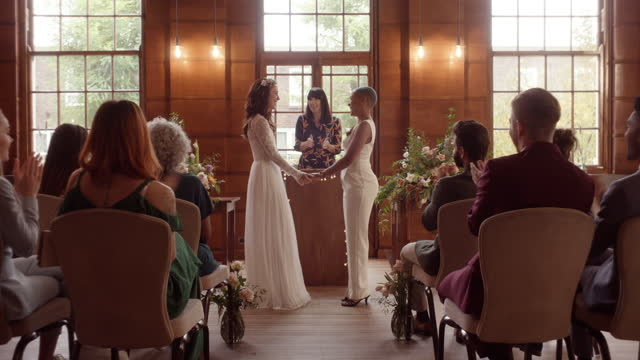 lesbian couple holding hands and kissing at wedding ceremony - wedding stock videos & royalty-free footage