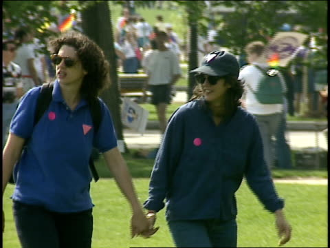 lesbian couple holding hands and walking through crowded park in washington dc at gay pride parade - 1993 stock-videos und b-roll-filmmaterial