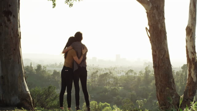 LGBT Lesbian couple hugging as they watch the sun go down on the city from the park