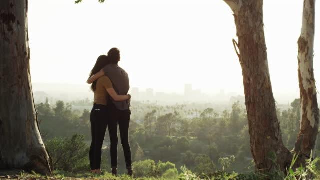 vídeos de stock, filmes e b-roll de lgbt lesbian couple hugging as they watch the sun go down on the city from the park - olhando para vista