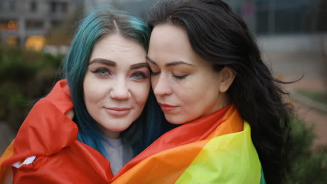 lesbian couple hugging covered with rainbow flag in public - spectrum stock videos & royalty-free footage