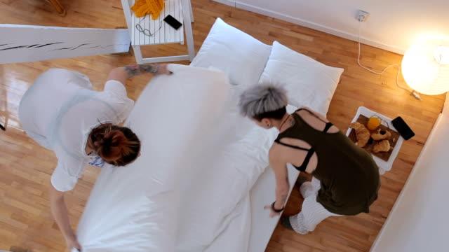 vídeos de stock, filmes e b-roll de casal de lésbicas fazendo sua cama - fazer