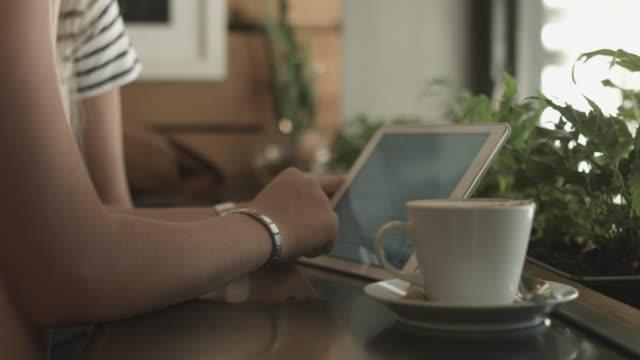 vídeos de stock e filmes b-roll de lesbian couple on tablet in coffee shop, tilt up - cabelo curto comprimento de cabelo
