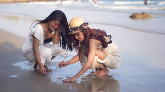 lesbisk par slappna av tid på stranden - gå tillsammans bildbanksvideor och videomaterial från bakom kulisserna