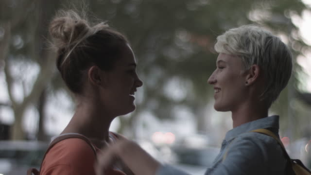 vidéos et rushes de lesbian couple say goodbye on street, close up - la vingtaine