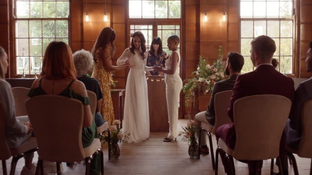 lesbian couple standing at altar receiving rings - full length stock videos & royalty-free footage