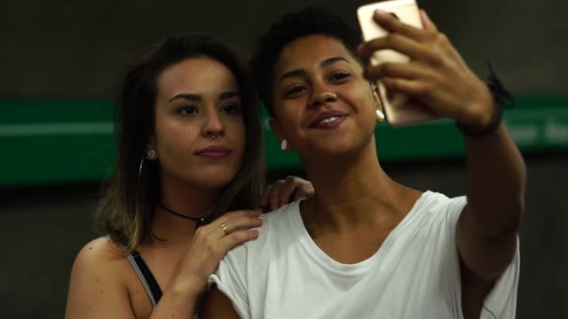 lesbian couple taking a selfie at subway station - dating stock videos & royalty-free footage