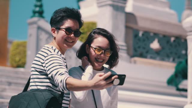 vidéos et rushes de couples lesbiennes prenant des selfies avec le smartphone - lieu de culte