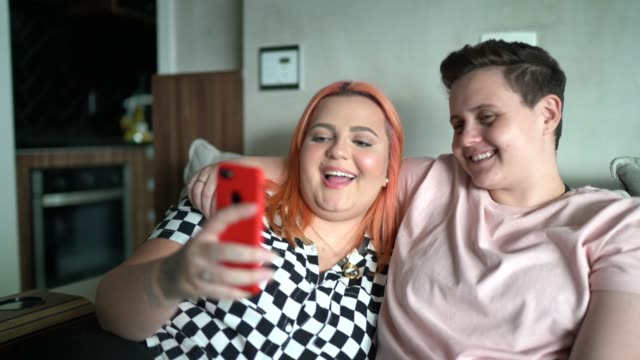 lesbian couple using mobile on sofa at home - generation z stock videos & royalty-free footage