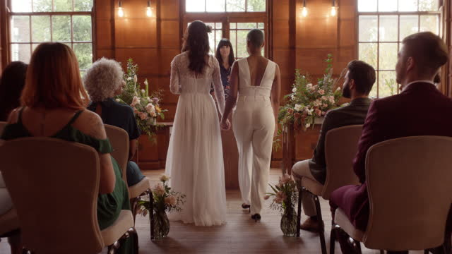lesbian couple walking up aisle at wedding ceremony - full length stock videos & royalty-free footage