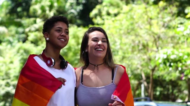 lesbian couple with rainbow flag - parade stock videos & royalty-free footage