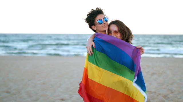 lesbian couple with rainbow flag - lesbica video stock e b–roll