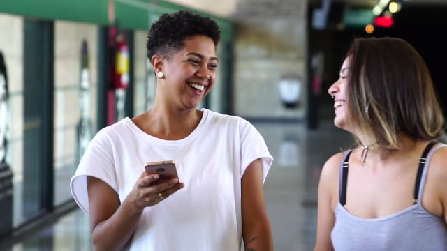 vídeos de stock, filmes e b-roll de casal de lésbicas/amigos na estação de metrô usando telefone inteligente - destino turístico