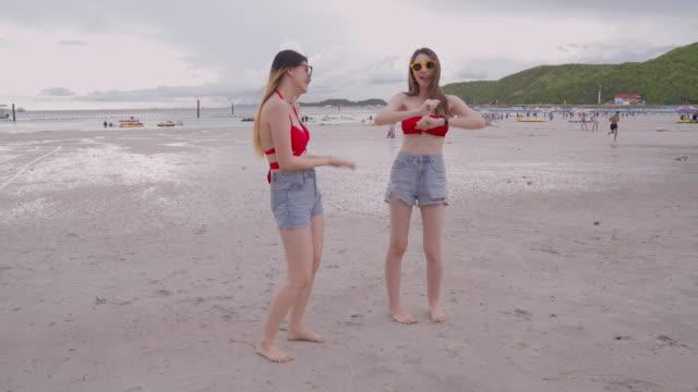 stockvideo's en b-roll-footage met lesbische liefhebbers staan dansen op het strand door de zee van thailand, vrouwen lgbt lesbische paar, lgbt gelijke rechten concept - politiek en staatsbestuur