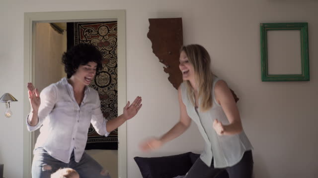 Lesbian mothers and son dancing in living room