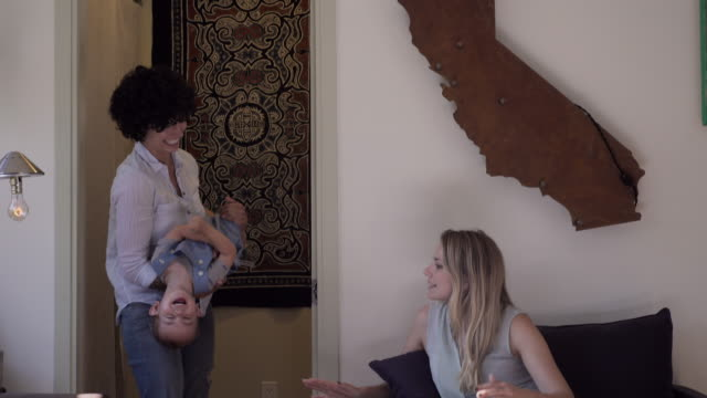 Lesbian mothers and son playing in living room
