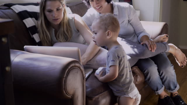 vídeos de stock, filmes e b-roll de lesbian mothers and son using laptop in living room - dois genitores