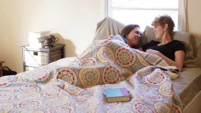LGBT lesbian young couple cuddling in bed.