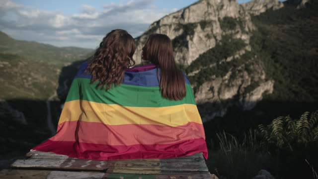 lesbians are on top of the mountain with rainbow flag - rainbow flag stock videos & royalty-free footage