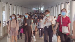 Less crowded Asian people wear face mask, walk in pedestrian walkway. Coronavirus disease Covid-19 pandemic outbreak effect, social distancing city life or PM 2.5 air pollution concept. 4K slow motion